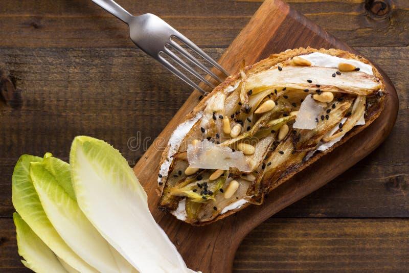 Fatia do pão com a chicória orgânica do assado, os pinhões e sésamo preto imagem de stock