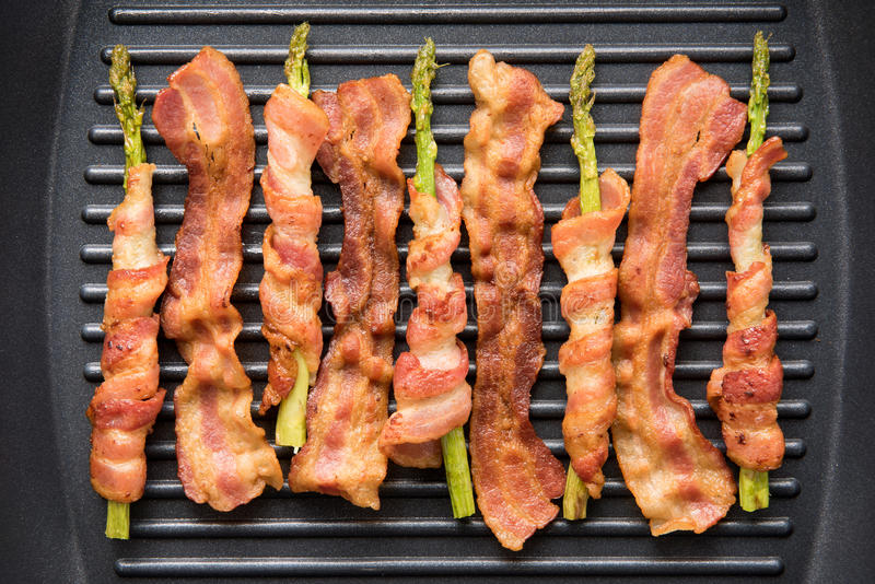 Fatia e aspargo do bacon envolvidos no bacon que está sendo cozinhado no fryin foto de stock royalty free