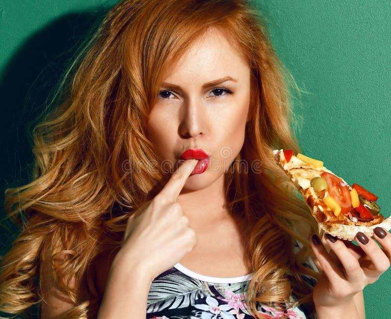 A fatia grande da posse bonita nova da mulher de fatia vegetal mexicana da pizza do material lambe um sinal saboroso do dedo no v imagens de stock royalty free