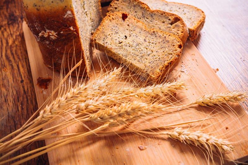 Fatia próxima de pão fresco com sementes de papoila e orelhas do trigo no fundo de madeira fotos de stock royalty free