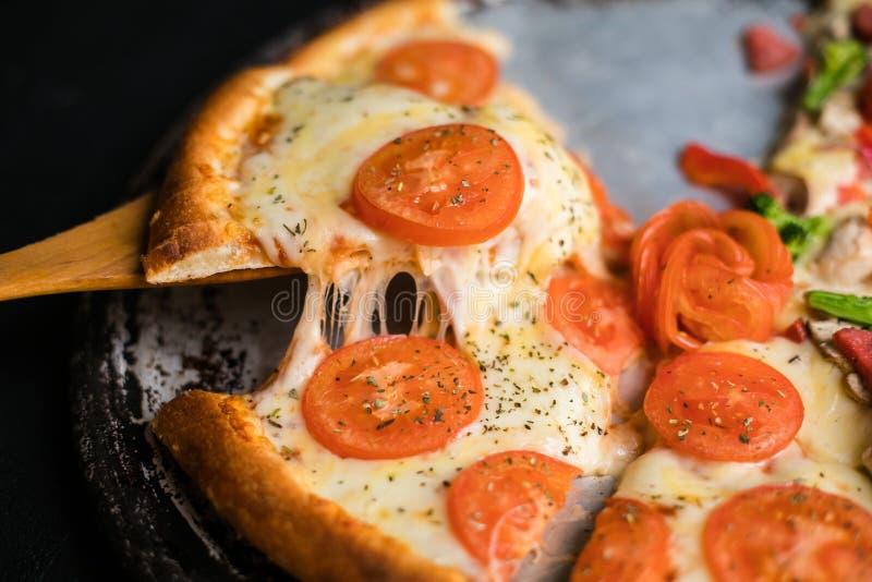 A fatia stringy do queijo levantada da pizza suprema completa do vegetariano cozeu fresco fora do forno ao lado dos ingredientes fotografia de stock royalty free