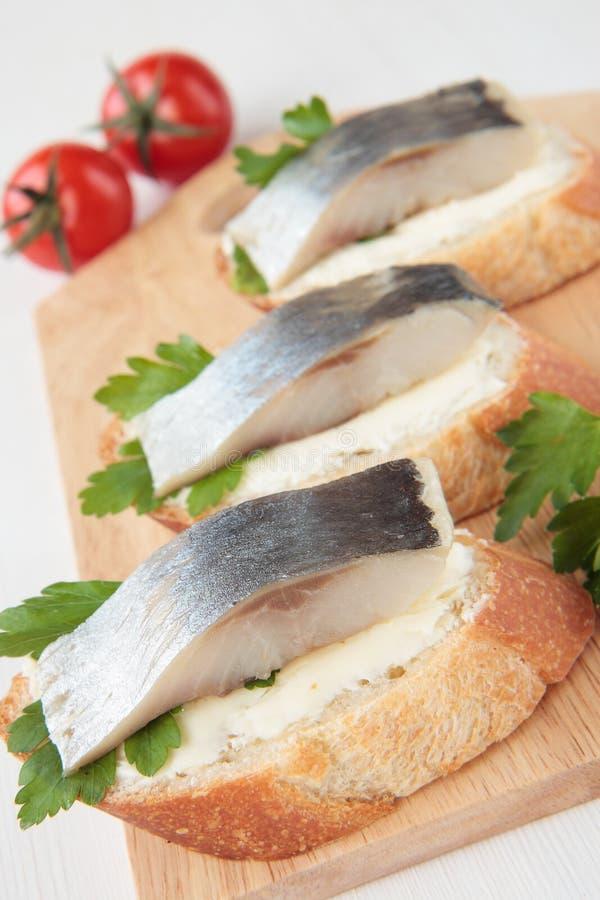 A fatia três de baguette com arenques e a salsa pôr manteiga fotografia de stock royalty free