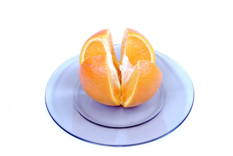 Fatias alaranjadas Corte em 4 porções da laranja, encontrando-se em uma placa em um fundo branco foto de stock royalty free