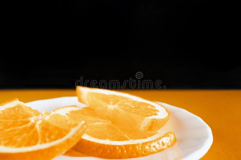 Fatias alaranjadas frescas em uma placa branca no fundo preto e alaranjado Alimento biológico saudável, café da manhã, conceito d foto de stock royalty free