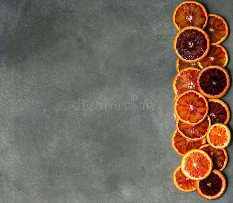 Fatias alaranjadas sicilianos suculentas do sangue no fundo cinzento Textura cortada da laranja pigmentada Fundo do citrino Copie imagem de stock royalty free