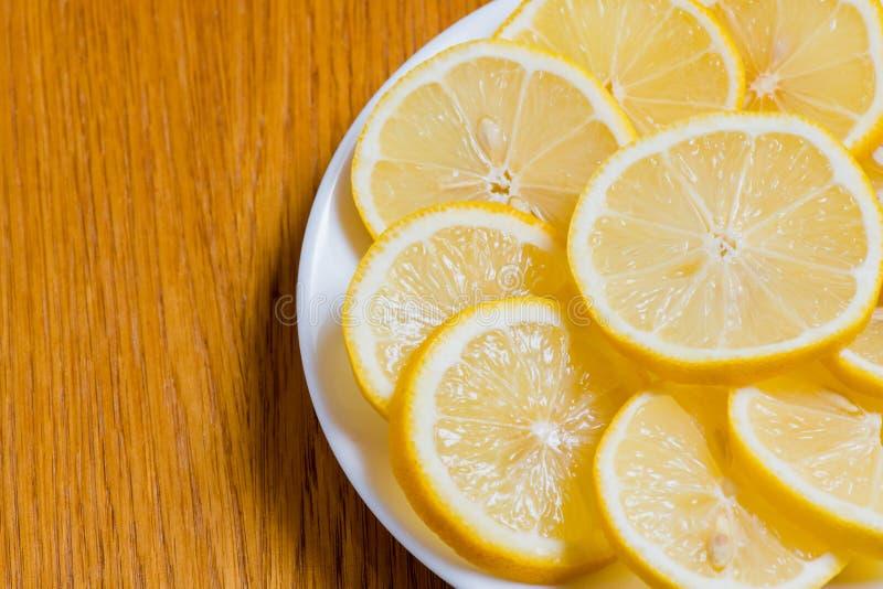 Fatias amarelas frescas dos lim?es em um fundo de madeira cal doce, vitamina c Fatia do lim?o fotos de stock royalty free