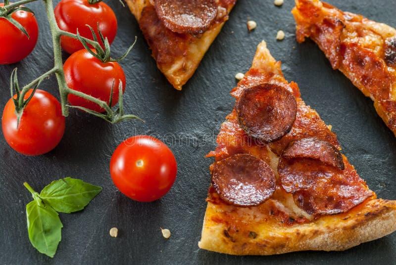 Fatias cozinhadas frescas deliciosas de pizza de pepperoni na ardósia com as folhas da pimenta vermelha e da manjericão de tomate imagem de stock