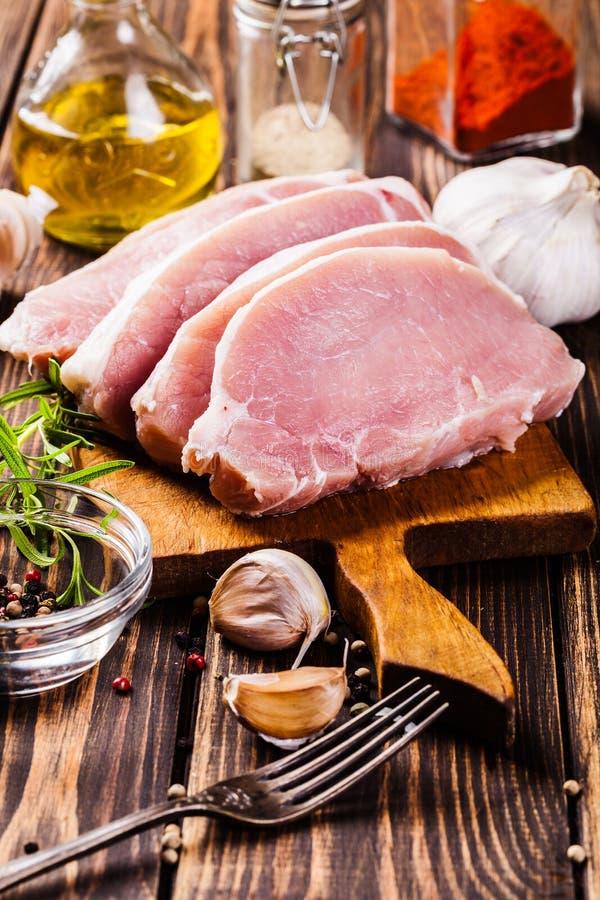 Fatias cruas da carne de porco em uma placa de desbastamento imagens de stock