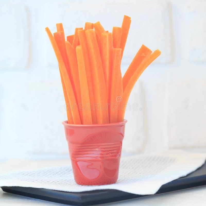 Fatias da cenoura em um vidro vermelho fotografia de stock royalty free