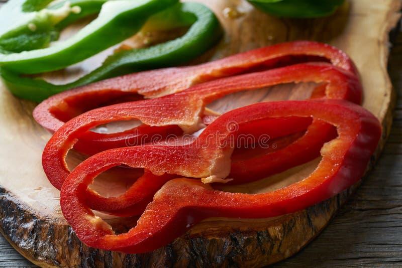 Fatias da pimenta verde e vermelha na placa de corte foto de stock royalty free