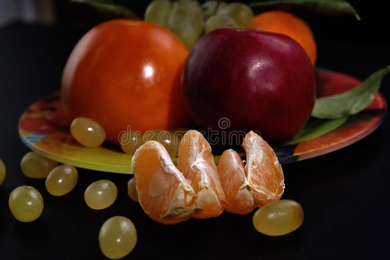 Fatias da tangerina e uvas verdes na frente de uma placa com fruto em um fundo preto, close-up fotos de stock royalty free