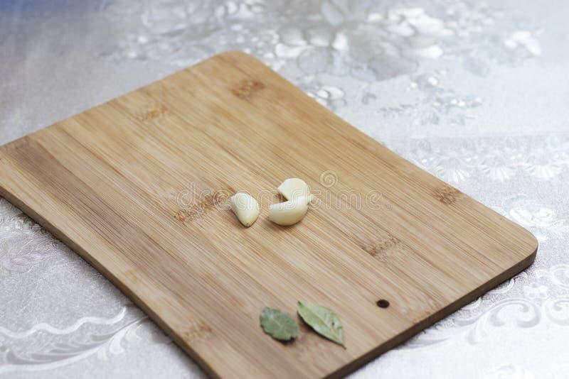 Fatias de alho e de verdes em uma placa de corte de madeira Alho fresco fotos de stock royalty free