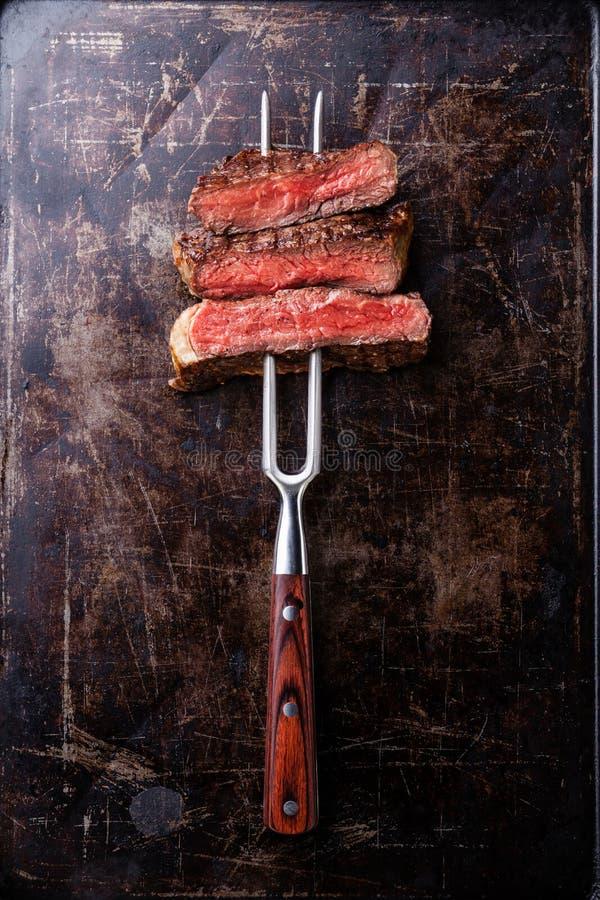 Fatias de bife raro na forquilha da carne fotos de stock royalty free