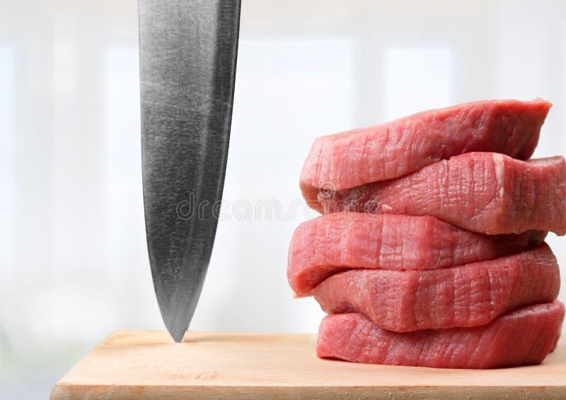 Fatias de carne crua com faca afiada imagem de stock