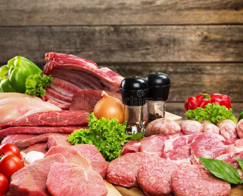 Fatias de carne crua com vegetais e especiarias imagens de stock