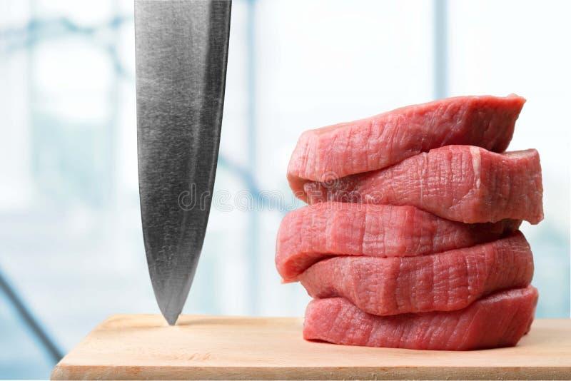 Fatias de carne crua e de faca na placa de corte foto de stock