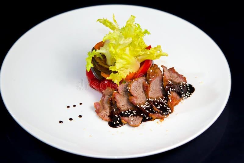 Fatias de carne fumado, servidas com guarnição da salada fresca, da paprika grelhada e da beringela, alimento preto do fundo foto de stock