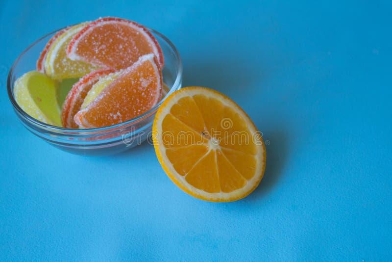 Fatias de doce de fruta limão e partes alaranjadas na placa Amarele imagens de stock royalty free