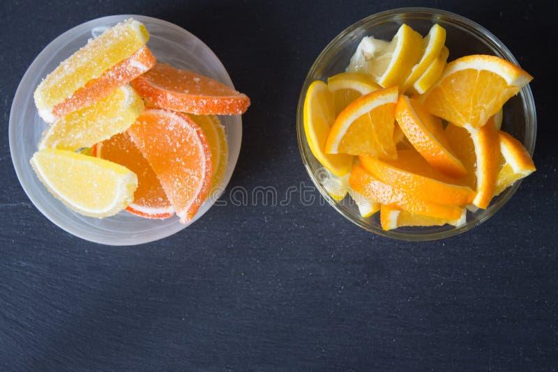 Fatias de doce de fruta limão e partes alaranjadas na placa Amarele foto de stock royalty free