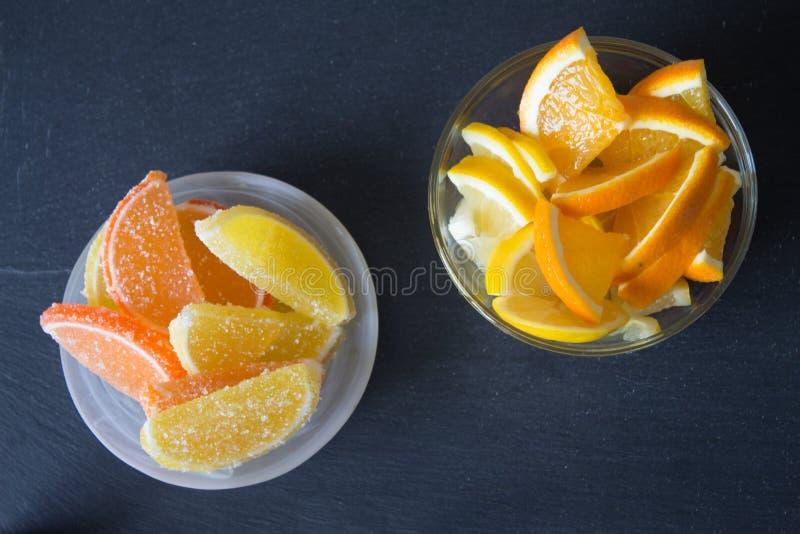 Fatias de doce de fruta limão e partes alaranjadas na placa Amarele foto de stock