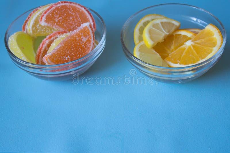 Fatias de doce de fruta limão e partes alaranjadas na placa Amarele fotos de stock