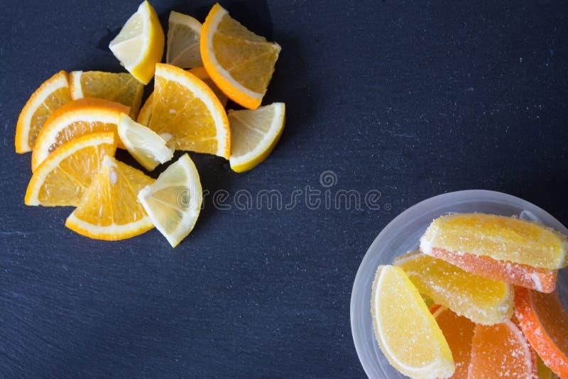 Fatias de doce de fruta limão e partes alaranjadas na placa Amarele imagens de stock