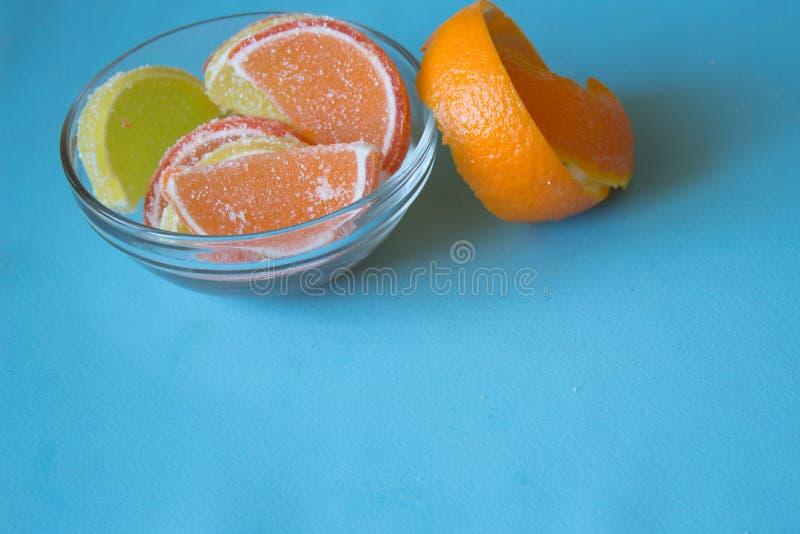 Fatias de doce de fruta limão e partes alaranjadas na placa com orangotango fotos de stock royalty free