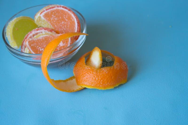 Fatias de doce de fruta limão e partes alaranjadas na placa com orangotango fotos de stock