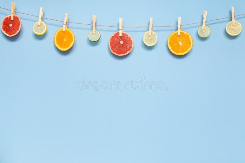 Fatias de laranja, de toranja, de limão e de cal pendurando em uma corda imagens de stock