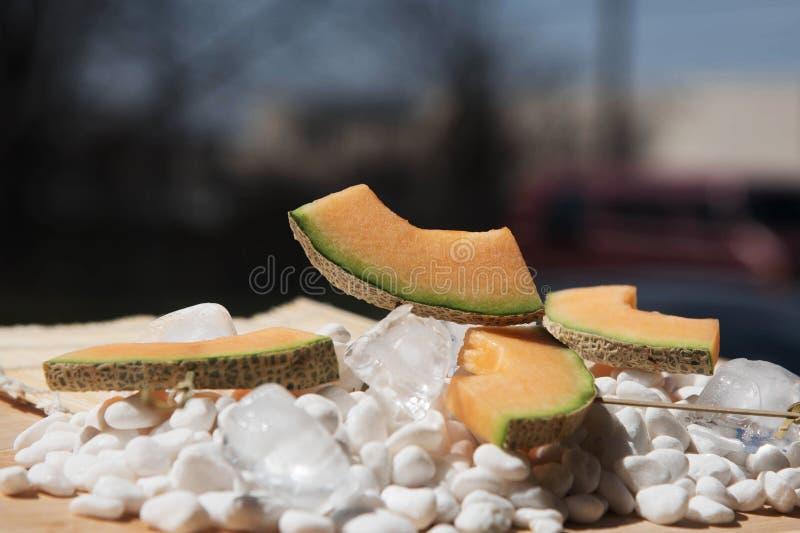 Fatias de melão em espetos nas pedras brancas fotografia de stock royalty free