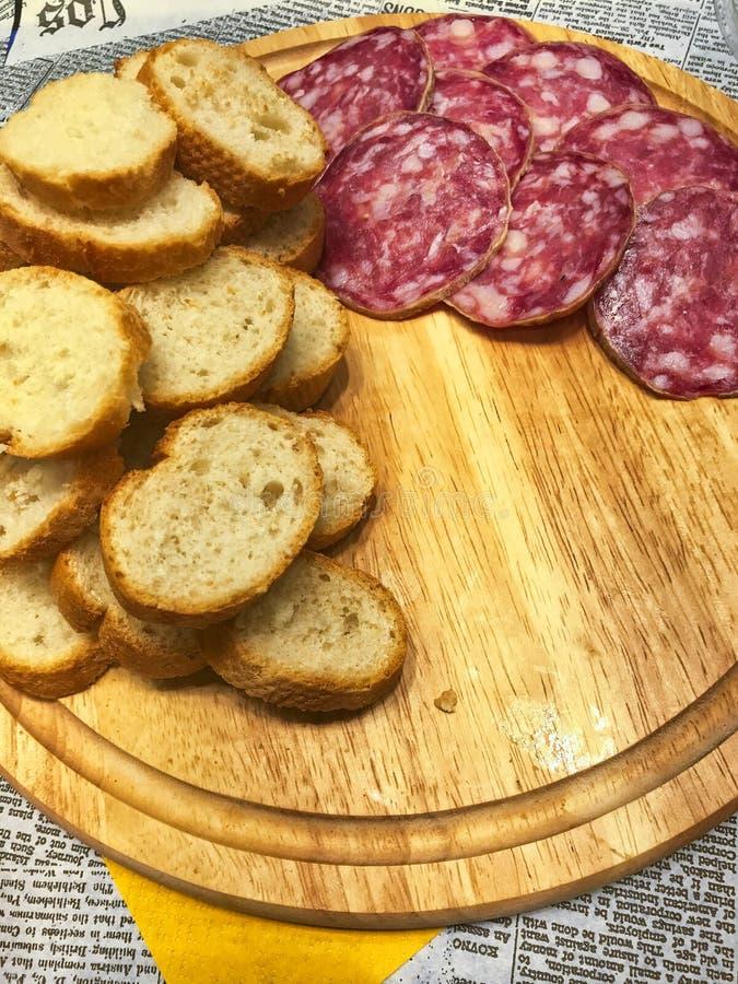 Fatias de pão e de salame tradicional italiano em uma placa de madeira fotografia de stock