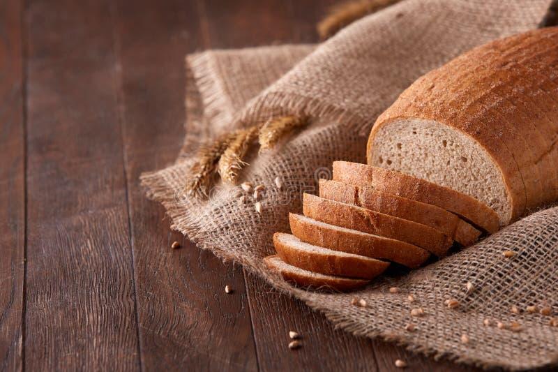 Fatias de pão na serapilheira na tabela de madeira escura, espaço para o texto foto de stock royalty free