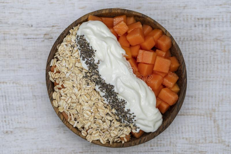 Fatias de papaia doce com flocos da aveia, sementes do chia e o iogurte branco na bacia do coco no fundo de madeira branco, fim a imagem de stock
