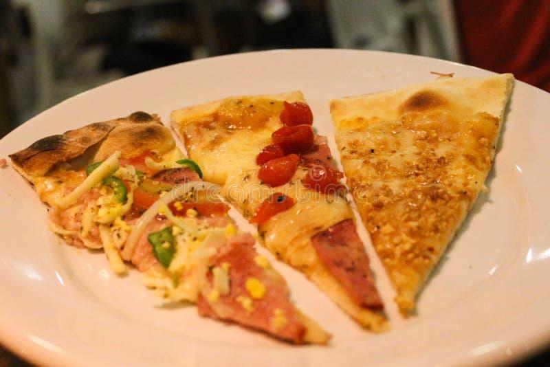 Fatias de pizza cozida fresca na placa branca fotos de stock