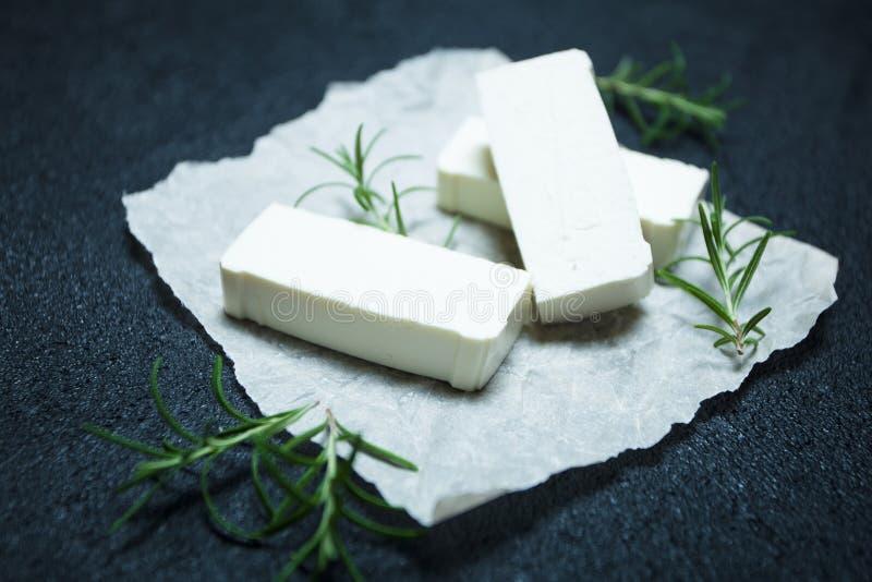Fatias de queijo de feta com alecrins no papel de pergaminho foto de stock royalty free