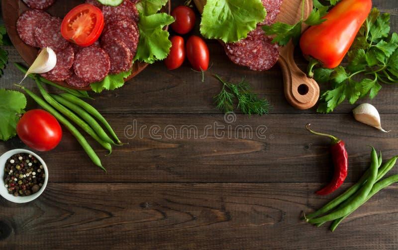 Fatias de salame com os vegetais no fundo de madeira foto de stock