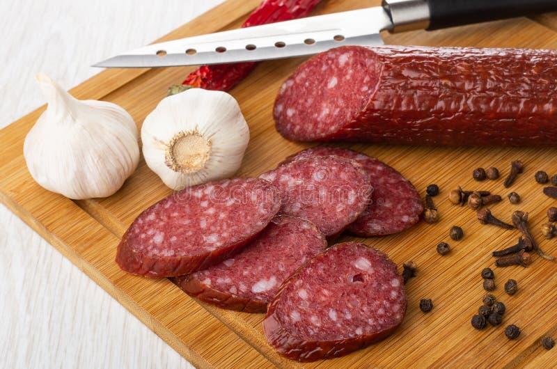 Fatias de salsicha, alho, pimenta de pimentão, pimenta preta, especiaria do cravo-da-índia, faca na placa de corte na tabela fotografia de stock royalty free