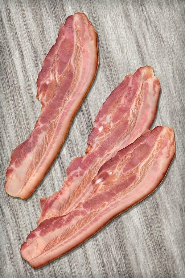 Fatias de toucinho do bacon da carne de porco ajustadas em Gray Wood Background descorado fotografia de stock