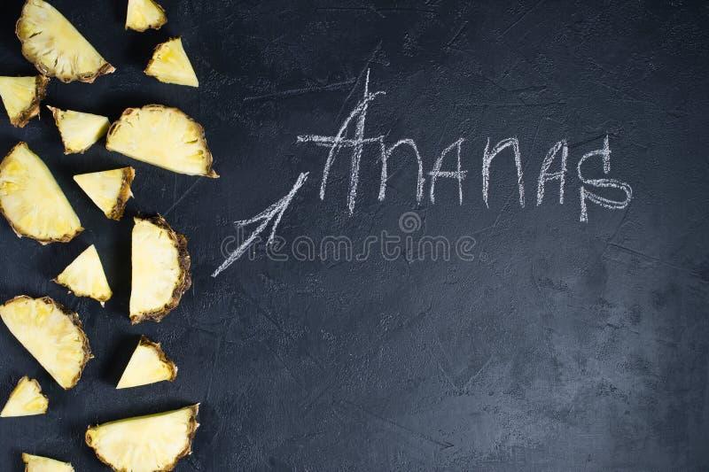 Fatias do abacaxi no fundo preto com espa?o para o texto e a inscri??o do giz fotos de stock