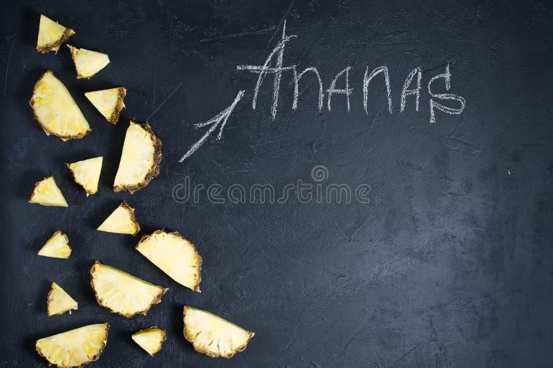 Fatias do abacaxi no fundo preto com espa?o para o texto e a inscri??o do giz fotografia de stock