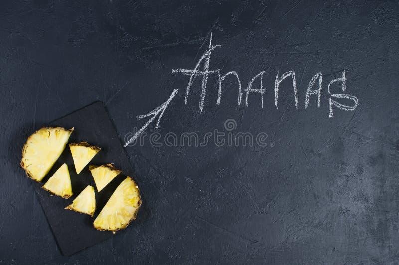 Fatias do abacaxi no fundo preto com espa?o para o texto e a inscri??o do giz imagem de stock