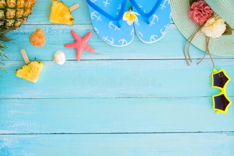 Fatias do abacaxi, shell, estrela do mar, deslizadores, chapéu de palha e óculos de sol na cor de madeira do azul da prancha imagens de stock