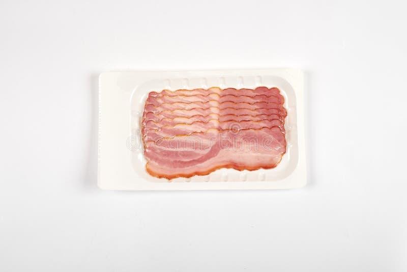 Fatias do bacon no pacote, isolado no fundo branco fotografia de stock