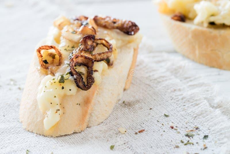 Fatias do Baguette com o mergulho de queijo caseiro feito do queijo macio francês, de cebolas caramelizadas e de ervas secadas fotos de stock royalty free