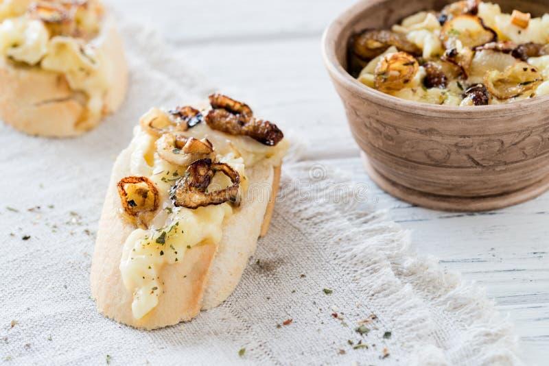 Fatias do Baguette com o mergulho de queijo caseiro feito do queijo macio francês, de cebolas caramelizadas e de ervas secadas fotografia de stock royalty free