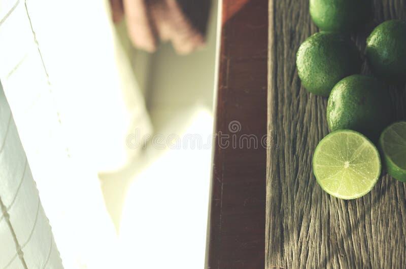 Fatias do cal na tabela de madeira A dieta da desintoxicação, cimenta fundos, fecha-se acima do tiro, fotos de stock royalty free