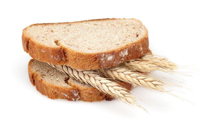 Fatias do pão com as orelhas do trigo no meio no fundo branco imagem de stock
