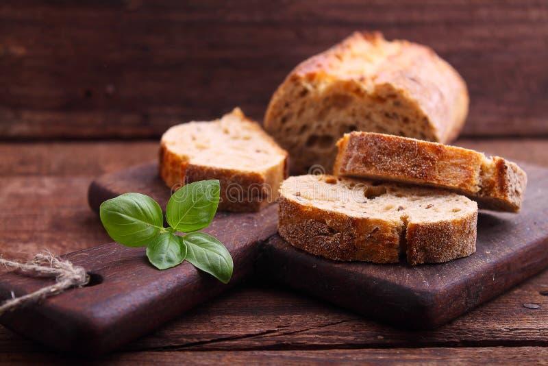 Fatias do pão em uma placa de madeira fotografia de stock