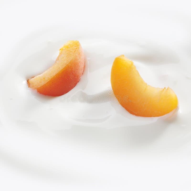 Fatias do pêssego que colocam no yogurt fotos de stock