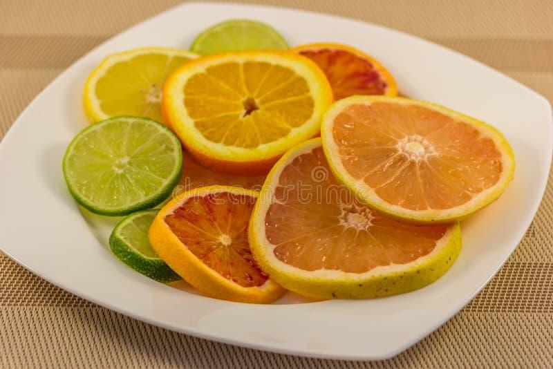 Fatias dos citrinos na placa foto de stock